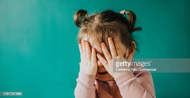 young girl covers her eyes with her hands - human finger stock pictures, royalty-free photos & images