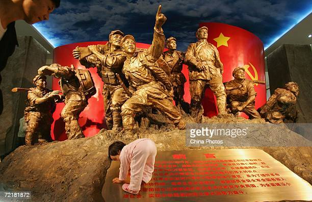 A young girl crawls on a billboard introducing the Long March at an exhibition to mark the 70th anniversary of the successful completion of the Long...