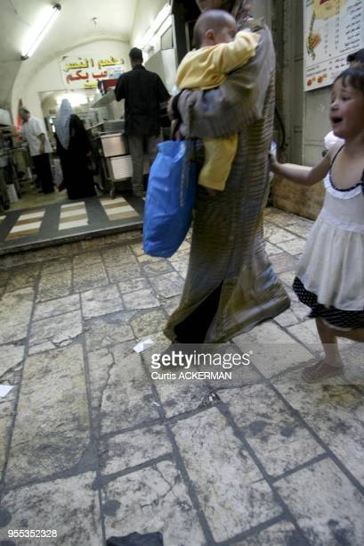 A young girl cries as she accompanies her mother his baby in arms while shopping in the Muslim Quarter of Jerusalem's Old City The Muslim Quarter...