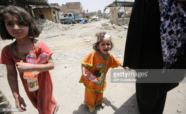 A young girl cries as she walks with others fleeing from the Old City of Mosul on July 2 as Iraqi government forces continue their offensive to...