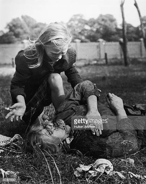 Young girl cries over her wounded and bleeding sister, who lies on the ground with her hand covered over a chest wound, during the Nazi invasion of...