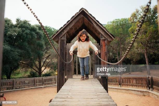 Young girl crossing a bridge