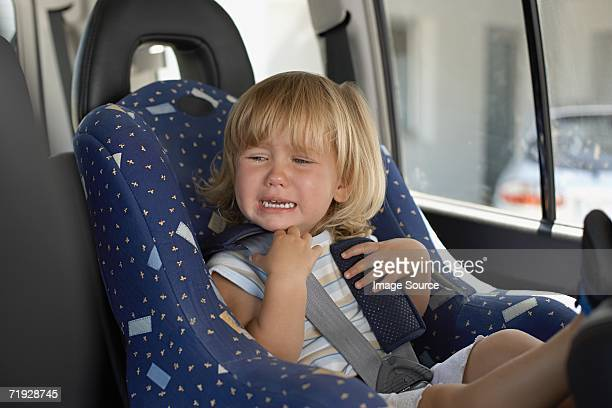 Young girl crying in her car seat