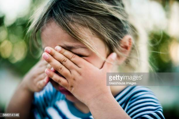 Young Girl Crying with Hands Covering Face