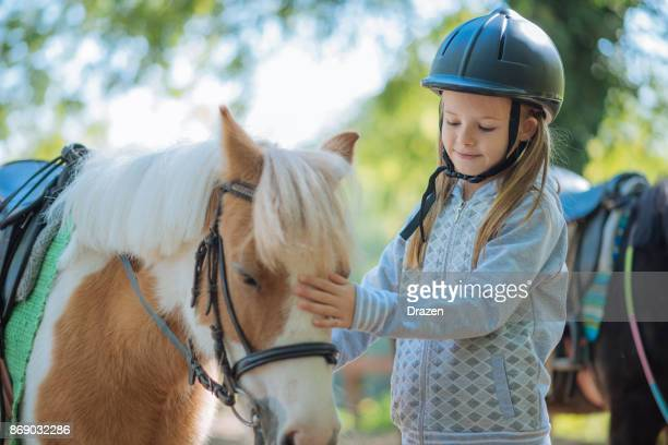 Young girl cuddling her pony horse