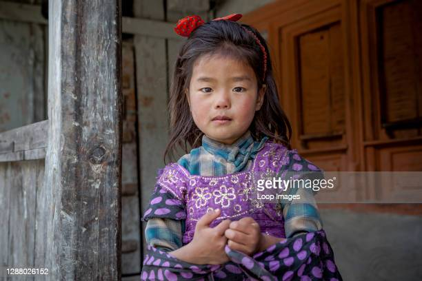 Young girl curious whilst standing on her porch in Kowang in Nepal.