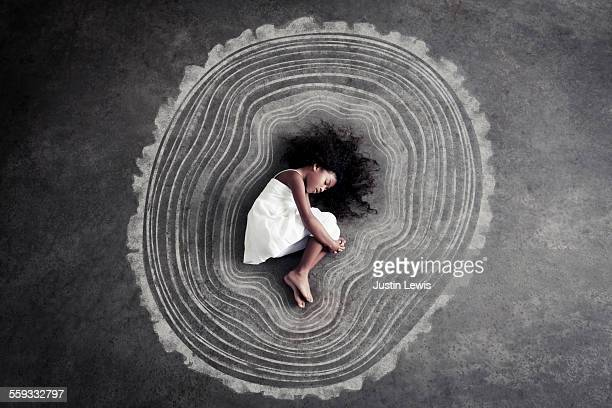 Young Girl curled inside graphic tree rings