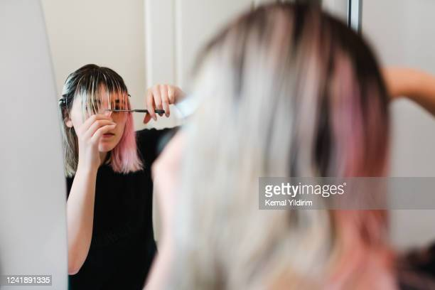 young girl cutting her own hair during lock down - fringing stock pictures, royalty-free photos & images