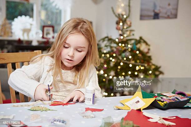 young girl cutting out paper preparing for christmas - craft stock pictures, royalty-free photos & images