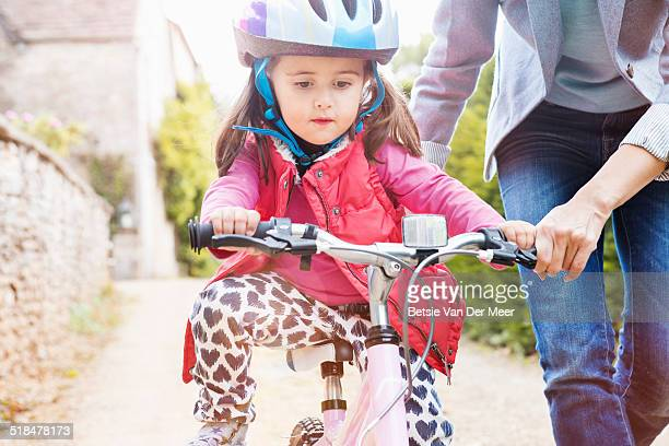 Young girl cycling, being supported by mother