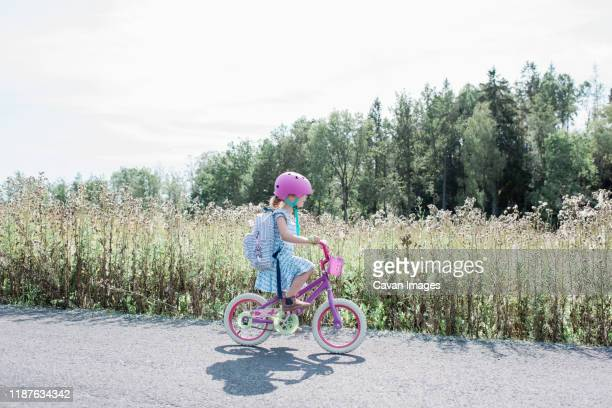 young girl cycling home from school along a country lane in summer - riding stock pictures, royalty-free photos & images