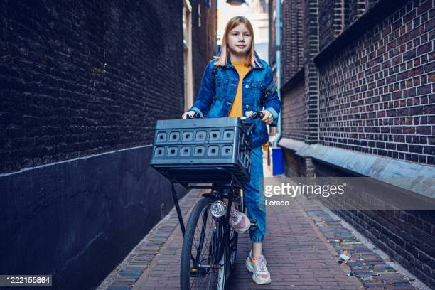 young girl cycling in an alley - district stock pictures, royalty-free photos & images
