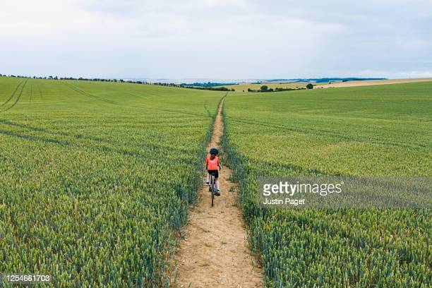 young girl cycling on track through field - bicycle stock pictures, royalty-free photos & images