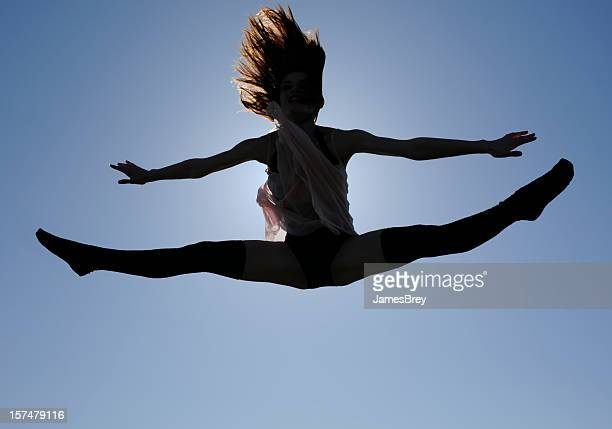 Young Girl Dancer's Amazing Splits Jump, Shilouetted in Blue Sky