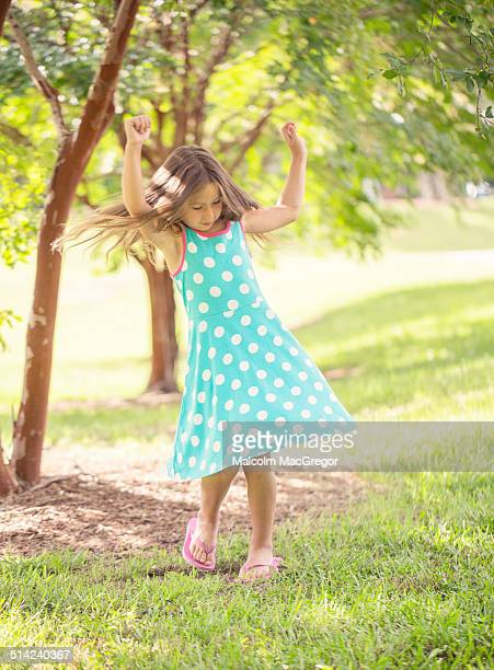 A young girl dances under trees