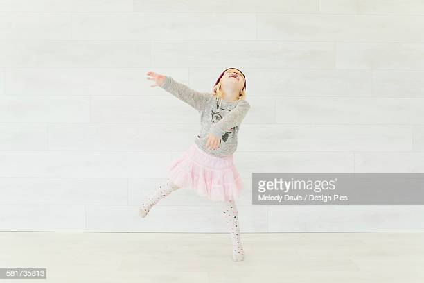 a young girl dancing in a pink skirt against a white wall - free up skirt pics stock photos and pictures