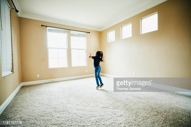 young girl dancing in empty room of new house during move - arrival stock pictures, royalty-free photos & images