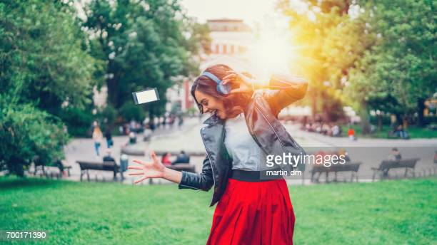 Young girl dancing to the music in the city park