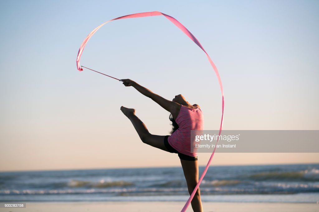 Young girl dancing with a ribbon on the beach at sunset : Photo