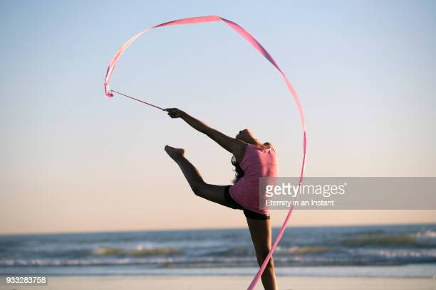 young girl dancing with a ribbon on the beach at sunset - gymnastique sportive photos et images de collection