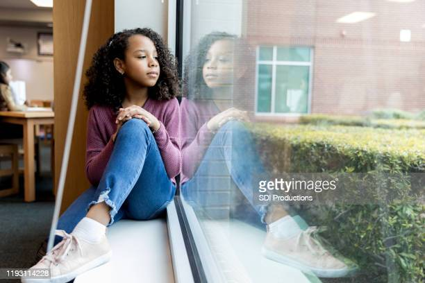 young girl daydreams while looking out library window - schoolgirl stock pictures, royalty-free photos & images