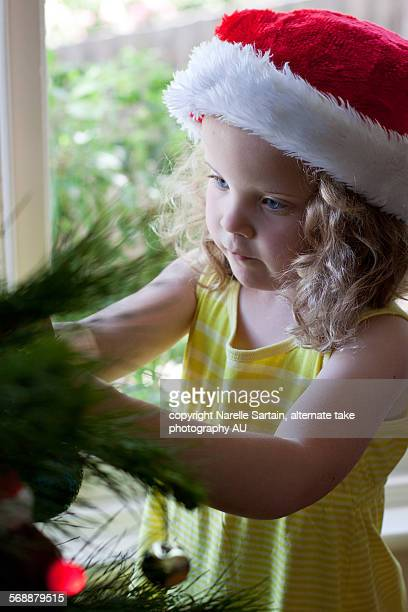 Young girl decorates christmas tree