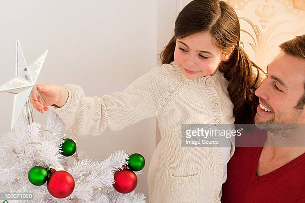 young girl decorating christmas tree - borough of lewisham stock pictures, royalty-free photos & images