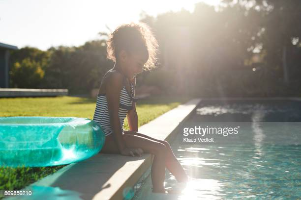 Young girl dipping her feet in the water