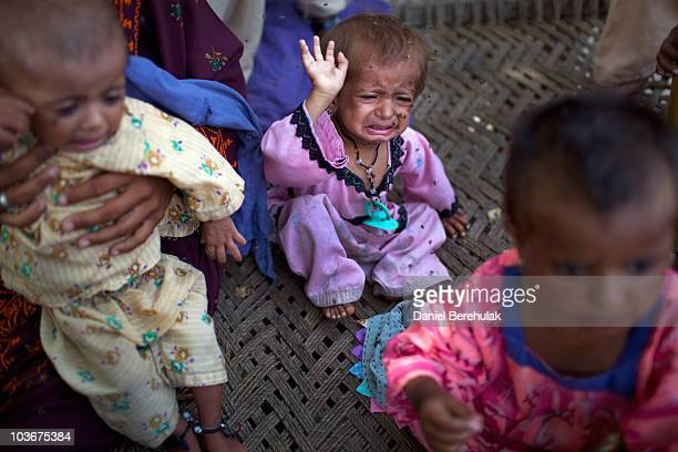 A young girl displaced by floods and stranded on land only accessible by air cries as she waves flies away from her face on August 27 2010 in Garhi...