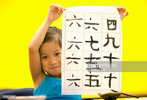 Young girl displays her calligraphy work.