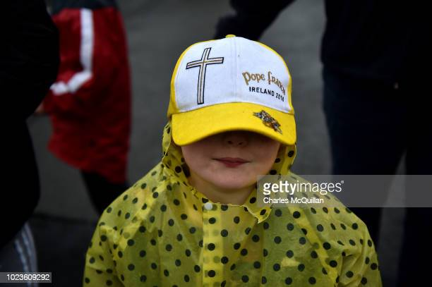A young girl displays her Pope baseball cap as pilgrims gather in the rain  ahead of f8b4b210409