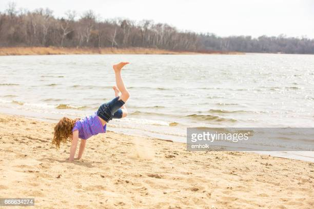 Young Girl Doing Cartwheels on Beach in Early Springtime