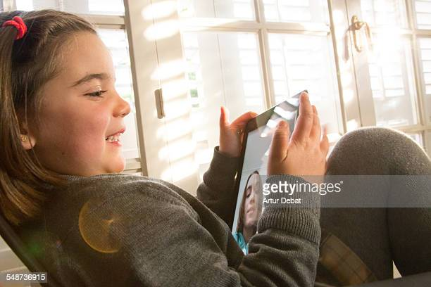 young girl doing facetime with her friend on ipad. - very young webcam girls stock photos and pictures