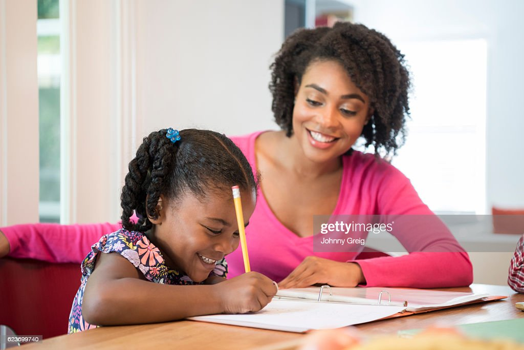 Young girl doing homework with her mother smiling and watching : Stock Photo