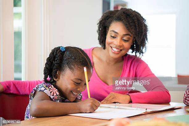 young girl doing homework with her mother smiling and watching - homeschool ストックフォトと画像