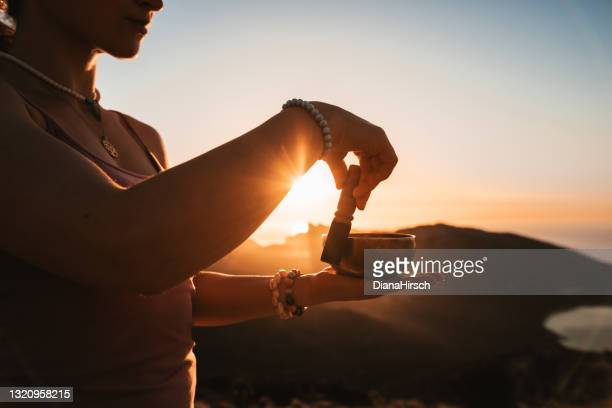 young girl doing meditation using a tibetan singing bowl during the sunrise in a mountainous landscape and seascape - rin gong stock pictures, royalty-free photos & images