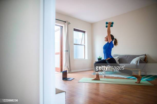 young girl doing online exercise session at home with dumbbells looking up - inquadratura fissa foto e immagini stock