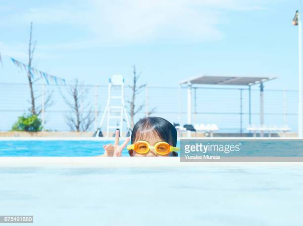 Young girl doing peace sign in swimming pool