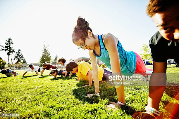 Young girl doing push ups with friends
