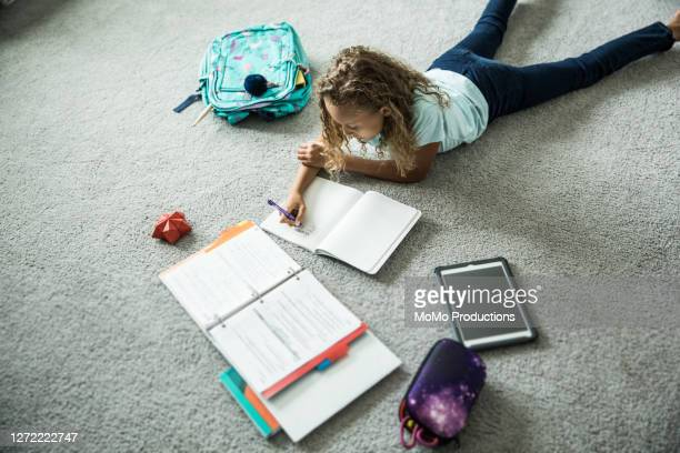 young girl doing schoolwork in her bedroom - learning disability stock pictures, royalty-free photos & images