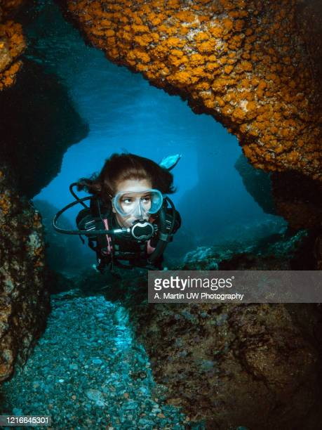 young girl doing scuba-diving and exploring an underwater cave with walls covered by orange coral. - aqualung diving equipment stock pictures, royalty-free photos & images