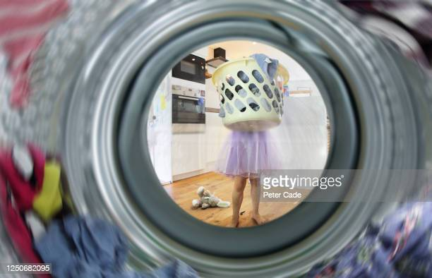 young girl doing the laundry - washing machine stock pictures, royalty-free photos & images