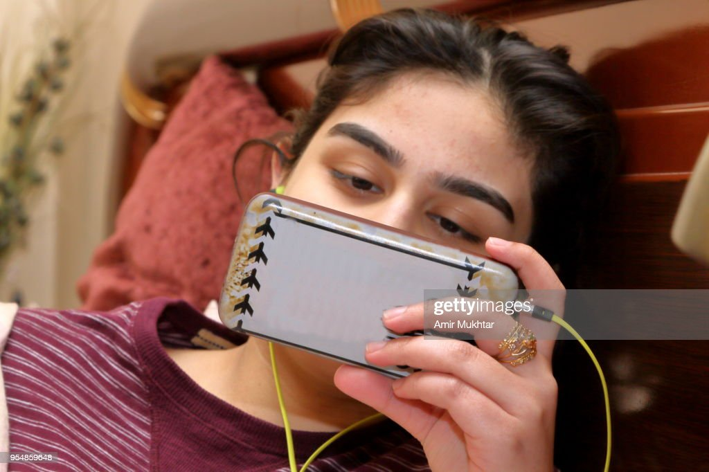 A young girl doing video chat or watching movie on cell phone : Stock Photo