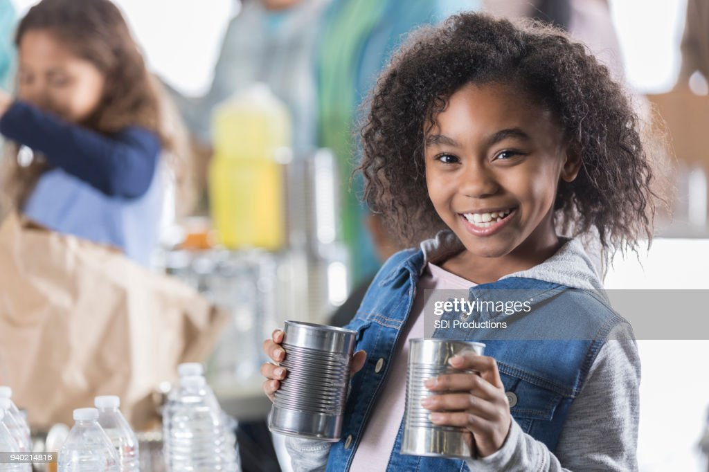 Young girl donates canned food items to food bank : Stock Photo