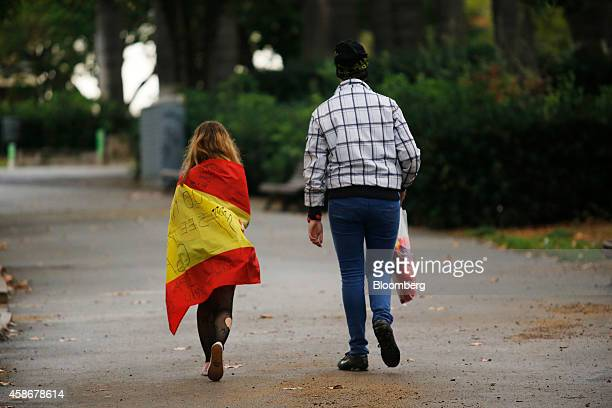 A young girl draped in the Spanish national flag left walks with a friend through a park on the eve of the Catalan proindependence referendum vote in...
