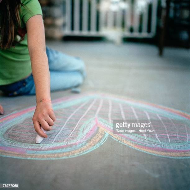 Young girl drawing a heart in chalk