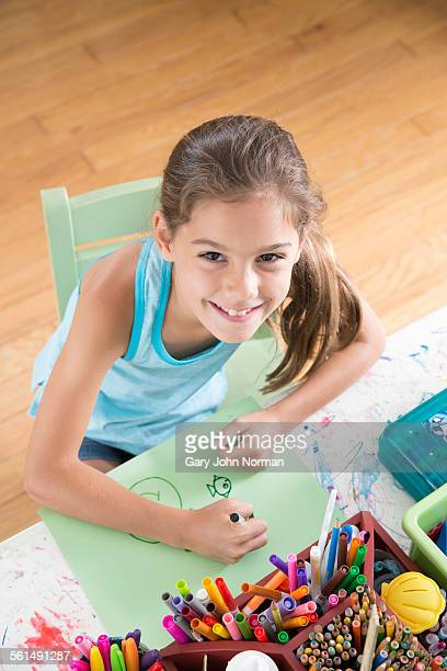 young girl drawing a picture at craft table. - sleeveless top stock photos and pictures