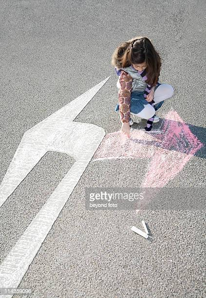 young girl drawing arrow in opposite direction of road sign