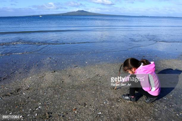 young girl drawing in the sand on a beach - rafael ben ari stockfoto's en -beelden