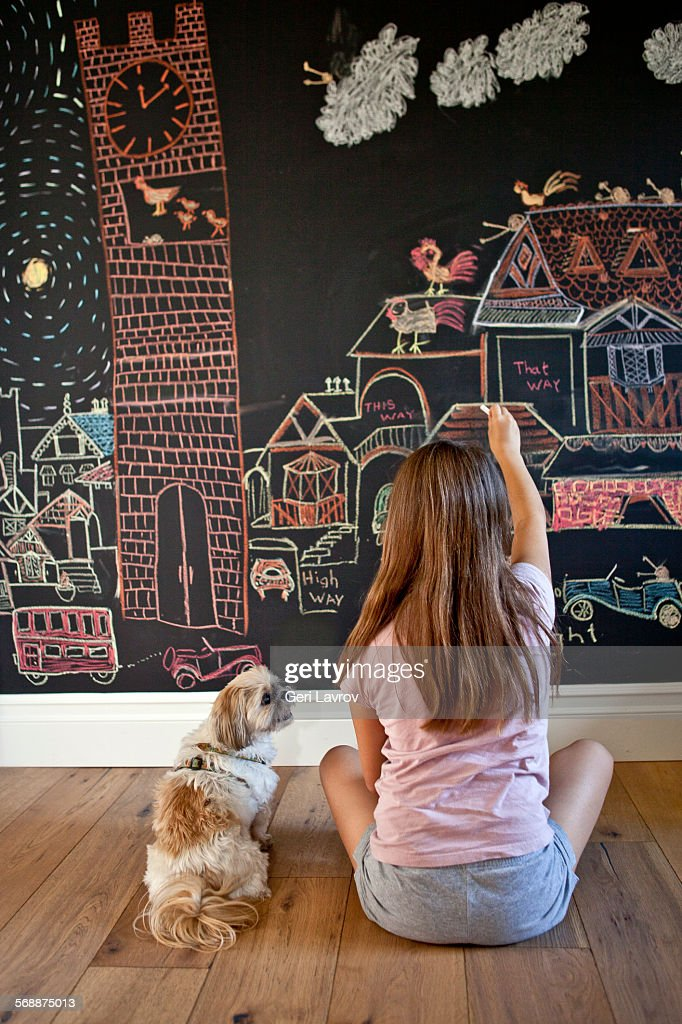 Young girl drawing on a blackboard : Stock Photo
